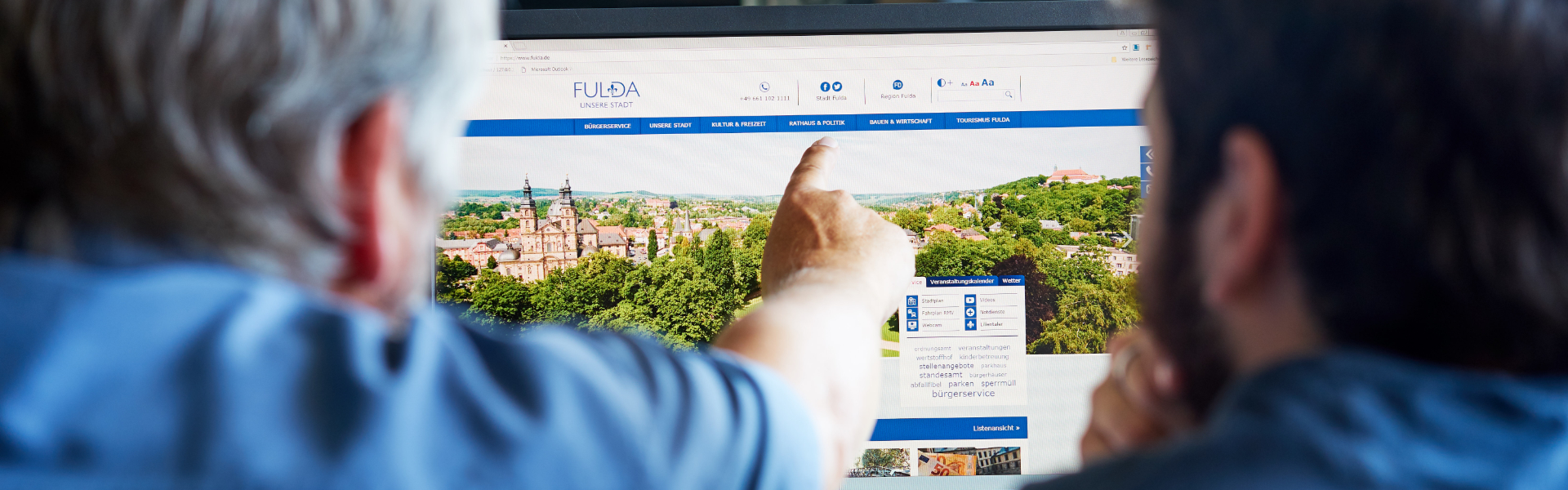 Zwei Männer sitzen vor einem Bildschirm, auf dem eine Webseite angezeigt wird. Der linke Mann deutet den Bildschirm.