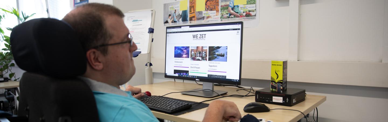 Werkstattmitarbeiter am PC-Arbeitsplatz schaut sich die Webseite WeZet an