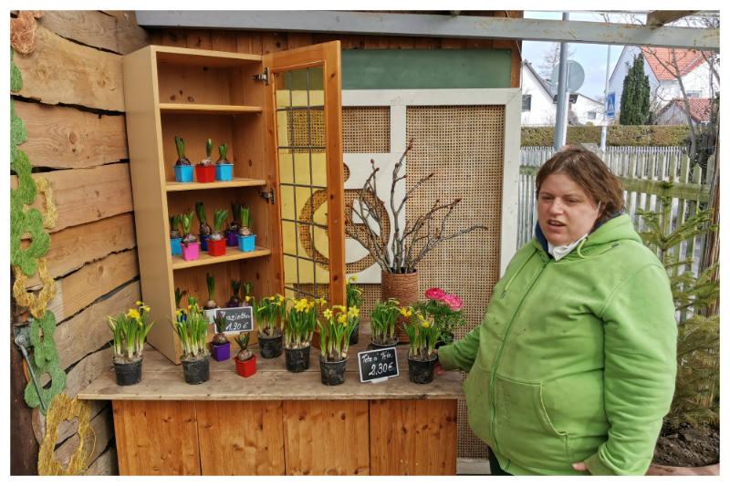 Larissa Mayr steht vor einem Angebotstisch mit Blumen