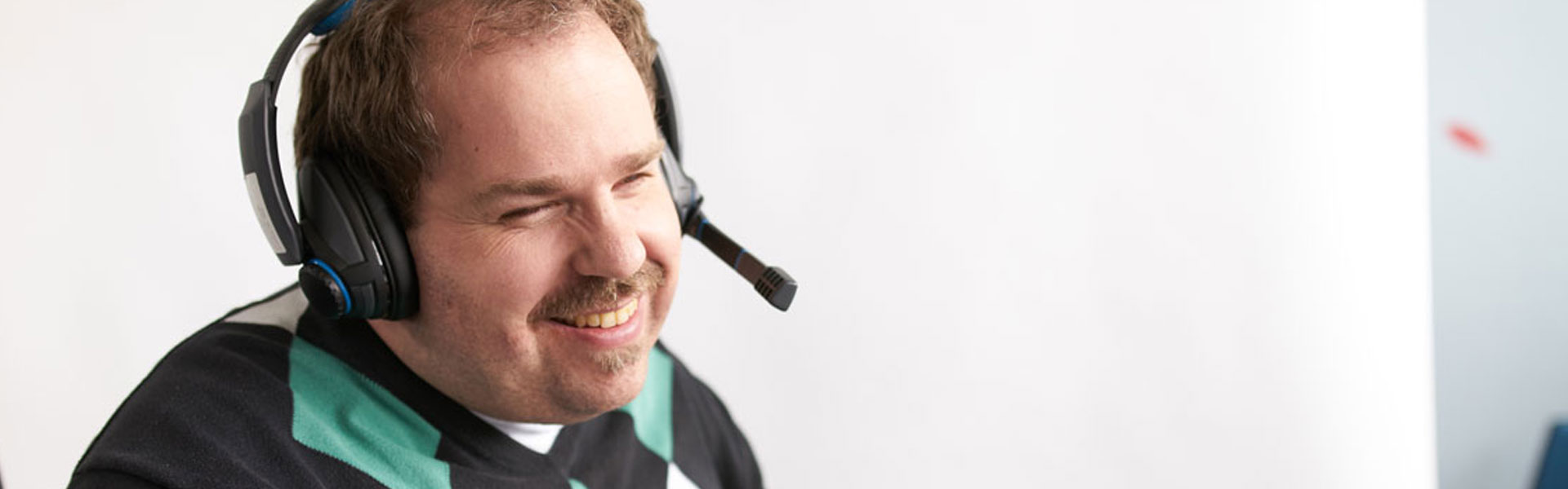 Sehbehinderter Mann hat lächelnd ein Headset auf
