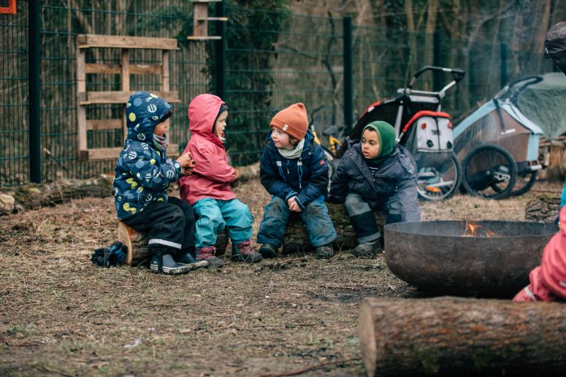 Vier Kinder an einer Feuerstelle im Wald