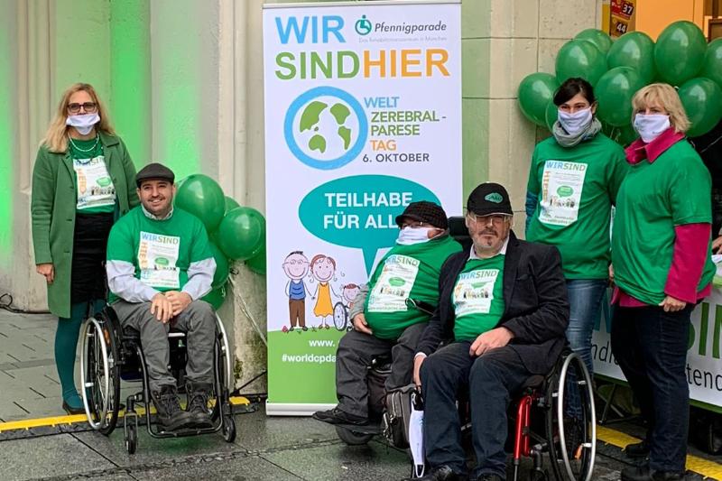 Sechs Personen in grünen Oberteilen vor dem Welt-CP-Tag-Aufsteller der Pfennigparade am Stachus