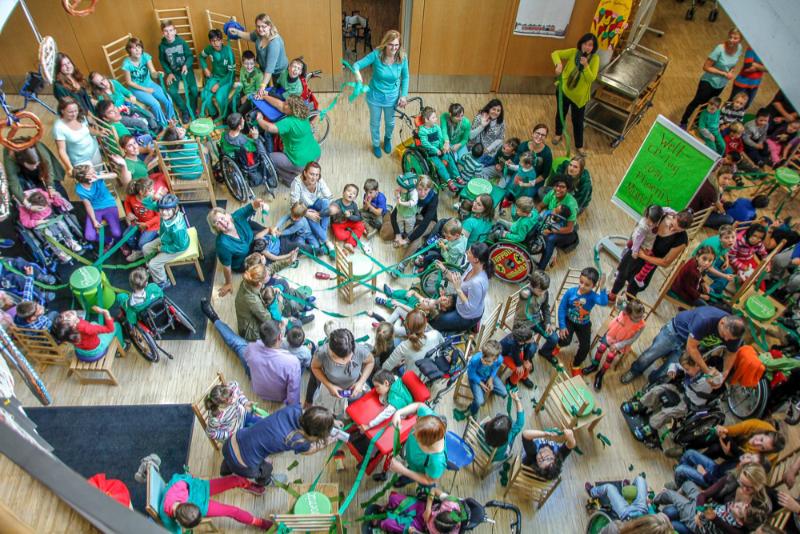 Raum voller Erwachsener und Kinder, die grüne Bänder halten, die sie verbinden