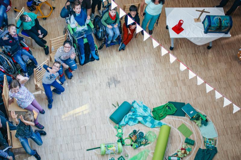 Einige Kinder in Rollstühlen und Sprossenstühlen winken in die Kamera, am Boden liegen viele grüne Dinge