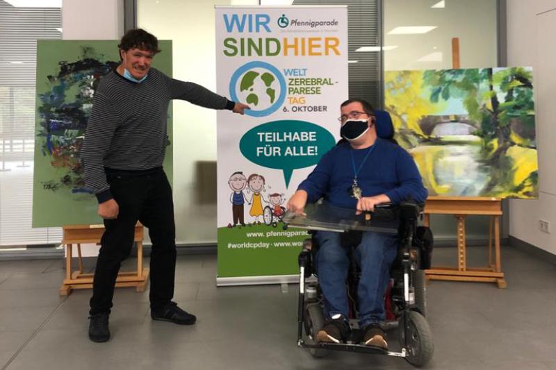 Ein Mann zeigt auf ein Plakat zum Welt-CP-Tag mit der Überschrift Wir sind hier Pfennigparade, daneben ein Mann im Rollstuhl