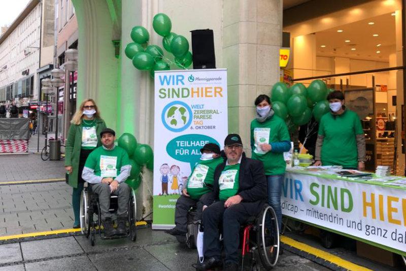 Sechs Personen in grünen T-Shirts vor dem Stand zum Welt-CP-Tag am Stachus