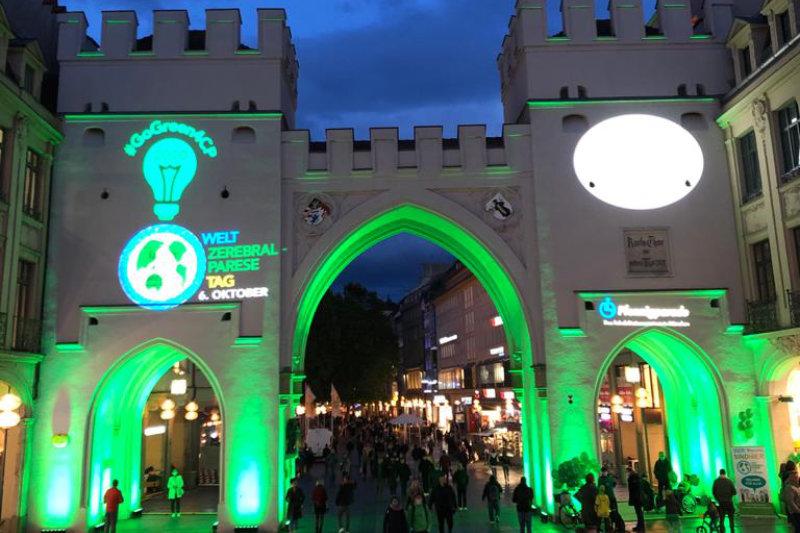 Karlstor bei Nacht mit grell grüner Beleuchtung Logo Pfennigparade und #GoGreen4CP Welt-CP-Tag 6. Oktober