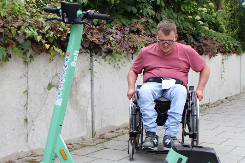 Mann im Rollstuhl steht auf dem Gehsteig vor einem E-Scooter