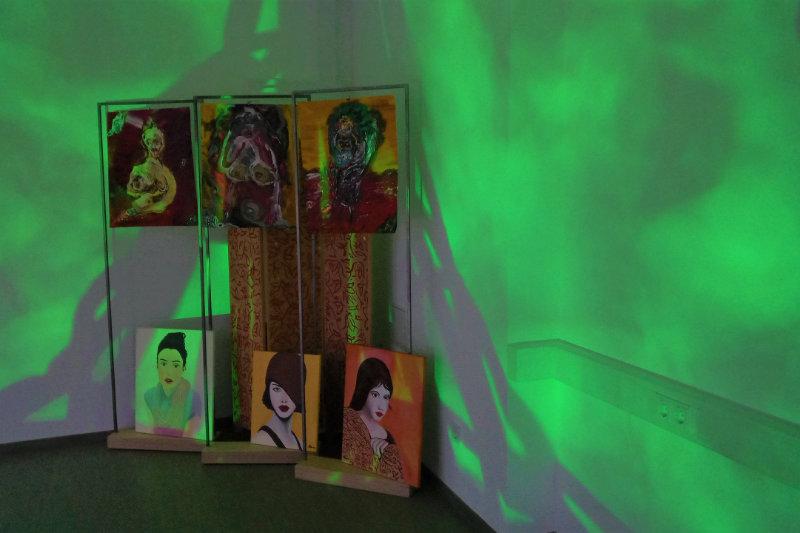 Sechs Portraits ausgestellt in einer Raumecke und grün beleuchtet