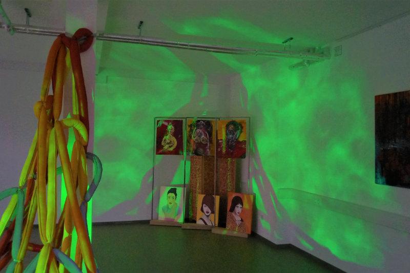 Kunstinstallation aus Stoffseilen im Hintergrund sechs Portraits in einer Raumecke mit grüner Beleuchtung im gesamten Raum