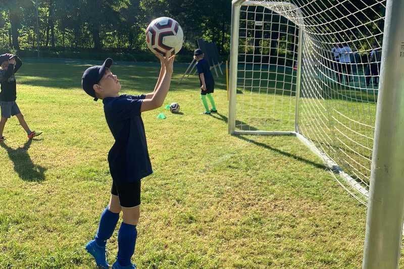 Junge mit Fußball in der Hand vor einem Tor auf dem Bolzplatz