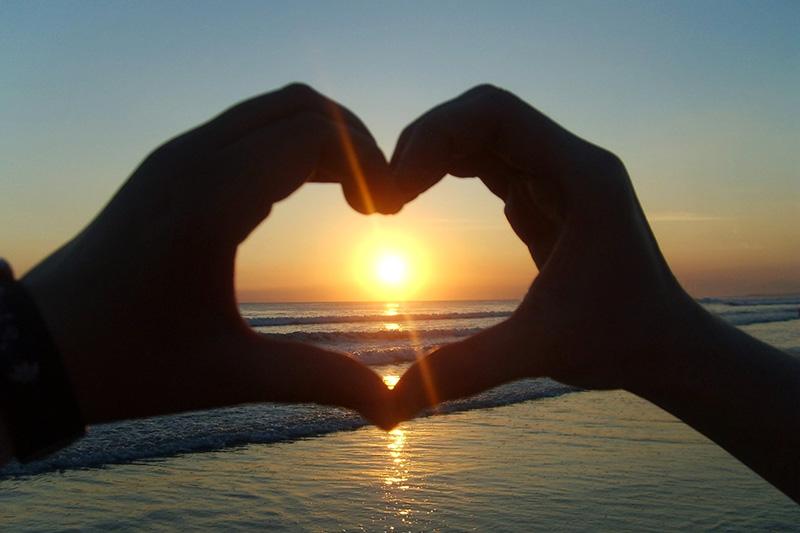 Zwei Hände formen ein Herz, durch das die Sonne hindurchscheint