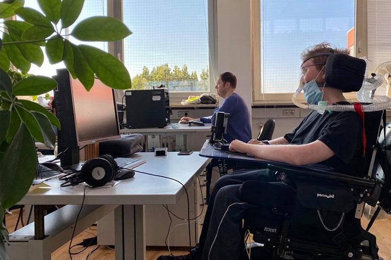 Zwei Männer sitzen an ihren Computern am Schreibtisch. Einer sitzt in einem Elektrorollstuhl, der andere an einem normalen Bürostuhl.