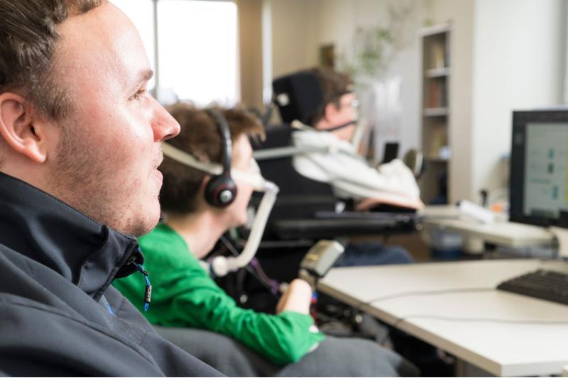 Drei junge Männer in Rollstühlen am PC-Arbeitsplatz