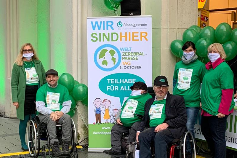 Sechs Menschen, davon drei Rollstuhlfahrer am Plakat zum Weltzerebraltag in München